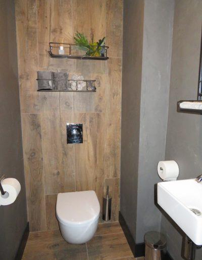 Foto 8. Hoe gaaf! Keramisch hout doorgetegeld op de achterwand van het toilet en aan de zijkant betonciré van vtwonen