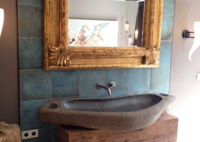 Badkamer met metallook tegels en keuken achterwand met mozaïek.