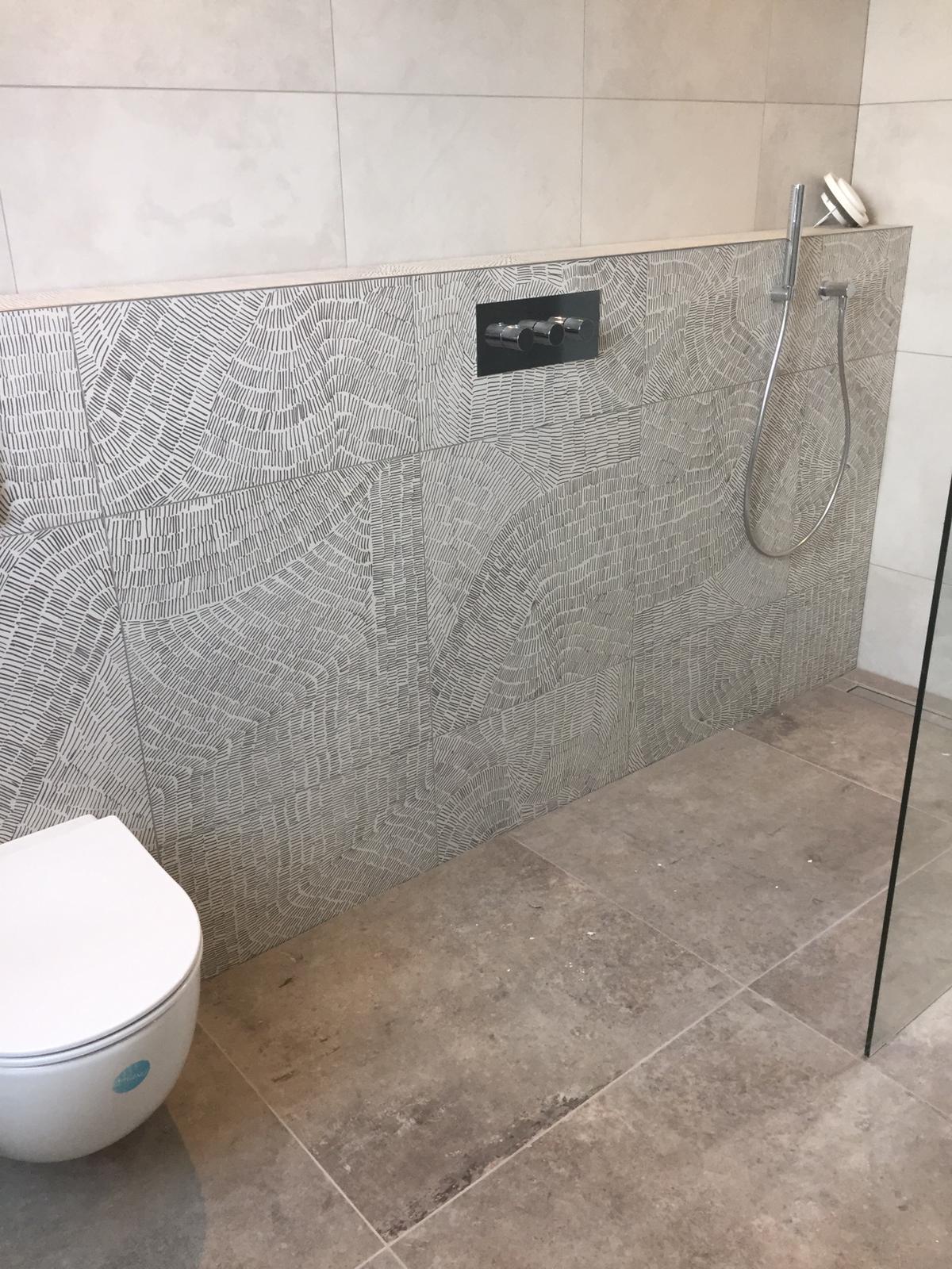 badkamer in aardetinten met o.a. een tegel van een Nederlandse student die een ontwerpwedstrijd heeft gewonnen.