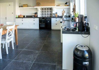 Woning met hardstenen keukenvloer en patroontegels in de hal